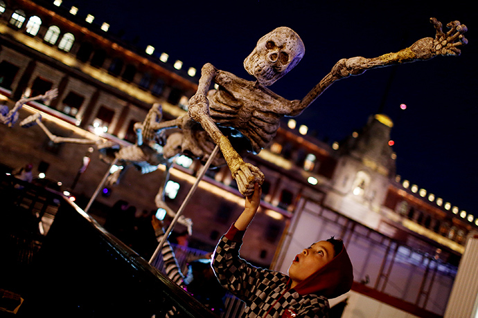 A child reacts while touching a skeleton model, which is part of an art installation to celebrate the Day of the Dead, in Zocalo Square, Mexico (Reuters / Tomas Bravo)