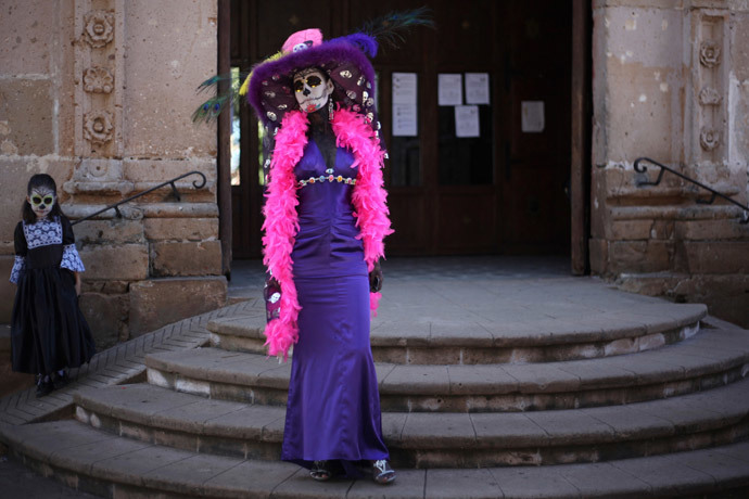 """People, with their faces painted as skulls, pose for a photo during the start of the """"Las Catrinas"""" festival, ahead of the Day of the Dead in Cupula on the outskirts of Morelia, Mexico (Reuters / Alan Ortega)"""