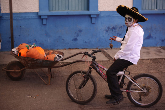 """A boy with his face painted as a skull poses for a photo during the start of the """"Las Catrinas"""" festival, ahead of the Day of the Dead in Cupula on the outskirts of Morelia, Mexico (Reuters / Alan Ortega)"""