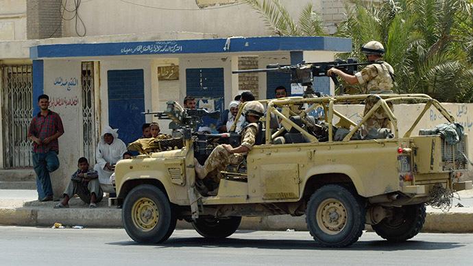 British soldiers wearing their combat helmets June 26, 2003 patrol in Amarah, 350 km southeast of Baghdad. (Reuters/Radu Sigheti)