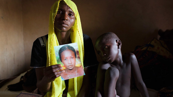 Rachel Daniel, 35, holds up a picture of her abducted daughter Rose Daniel, 17, as her son Bukar, 7, sits beside her at her home in Maiduguri (Reuters / Joe Penney)