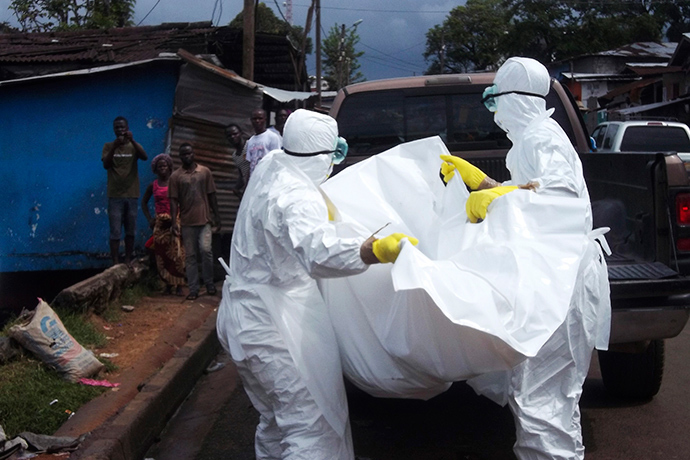 Health workers remove the body of a man believed to have died from the Ebola virus at a street in Monrovia, Liberia, October 27, 2014 (Reuters / James Giahyue)