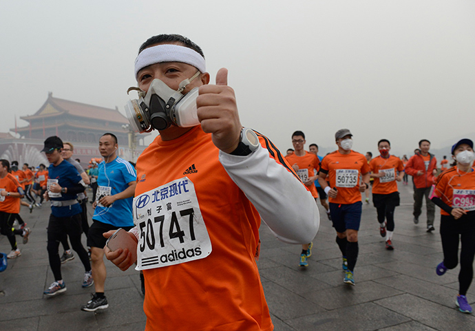 Participants wearing masks during a hazy day at the Beijing International Marathon in front of Tiananmen Square, in Beijing, October 19, 2014 (Reuters / Stringer)