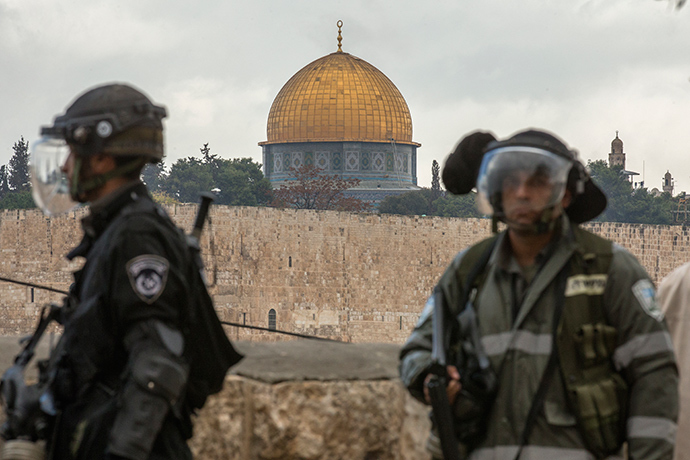 Israeli security forces keep watch backdropped by the Dome of the Rock mosque during Friday noon prayers in the east Jerusalem neighbourhood of Ras al-Amud on October 31, 2014, following restrictions by Israeli police to allow entry to men only above 50-year-old wanting to access the Al-Aqsa Mosque compound. Israeli police deployed heavily around Jerusalem's flashpoint Al-Aqsa mosque compound as it reopened today for Muslim prayers after a rare closure during clashes over the killing of a Palestinian by security forces (AFP Photo / Jack Guez)