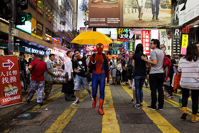 A pro-democracy supporter dressed as comic book character Spider-Man carries a yellow umbrella, regarded a symbol of the Occupy civil disobedience movement, on a road blocked by protesters at Mongkok shopping district in Hong Kong October 24,2014 (Reuters / Tyrone Siu)