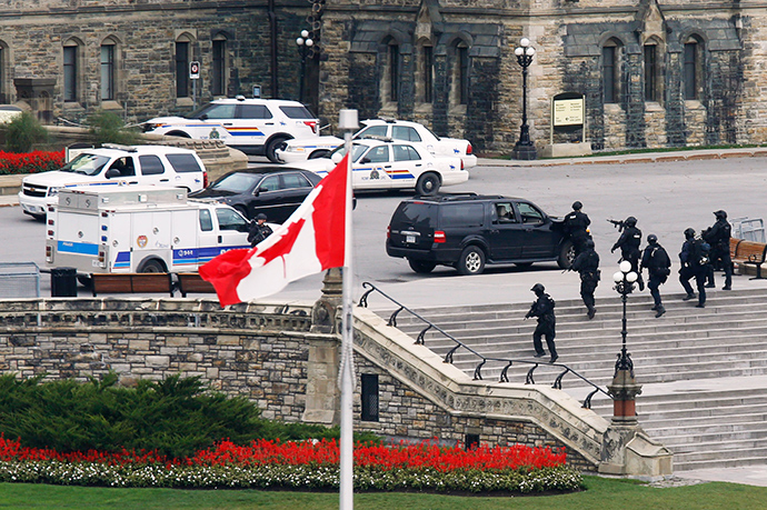 Armed RCMP officers approach Centre Block on Parliament Hilll following a shooting incident in Ottawa October 22, 2014 (Reuters / Chris Wattie)