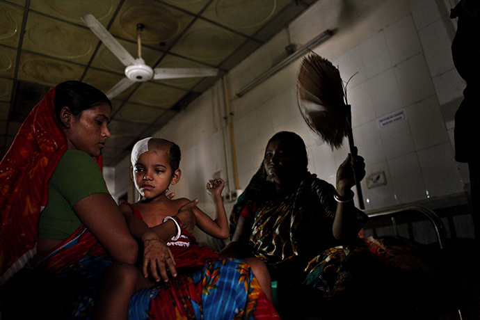 A Bangladesh woman fans a sick child during a power blackout at a hospital in Dhaka on November 1, 2014 (AFP Photo)
