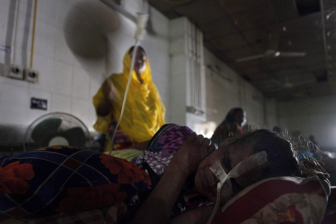 A Bangladesh patient lies on her bed during a power blackout at a hospital in Dhaka on November 1, 2014 (AFP Photo)