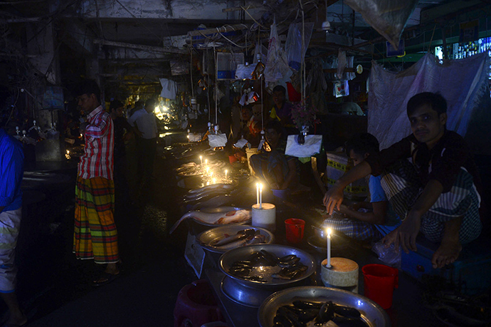 Bangladesh fishmongers light their fish stalls with candles during a power blackout in Dhaka on November 1, 2014 (AFP Photo / Munir uz Zaman)