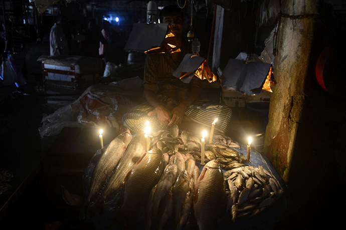 A Bangladesh fishmonger lights his fish stall with candles during a power blackout in Dhaka on November 1, 2014 (AFP Photo / Munir uz Zaman)