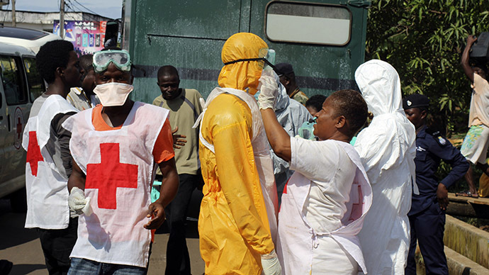 A health worker fixes another health worker's protective suit in the Aberdeen district of Freetown, Sierra Leone, October 14, 2014. (Reuters/Josephus Olu-Mammah)