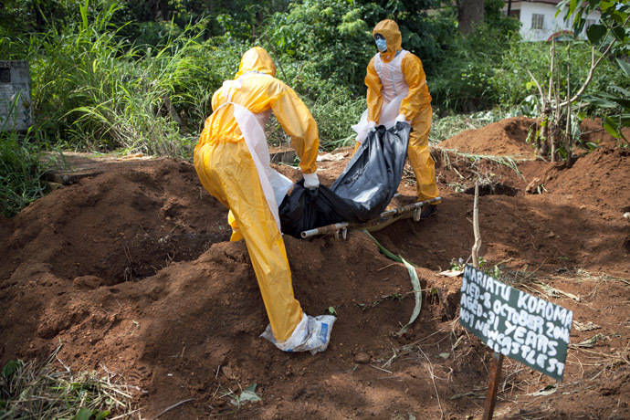 A team of funeral agents specialised in the burial of victims of the Ebola virus put a body in a grave at the Fing Tom cemetery in Freetown, on October 10, 2014. (AFP Photo)
