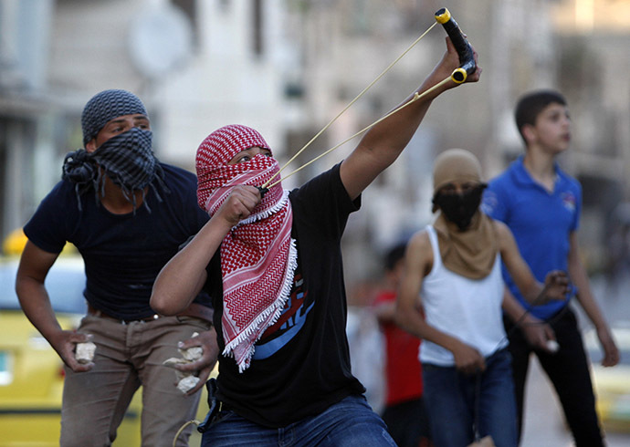 A Palestinian protester uses a slingshot to hurl a stone at Israeli troops during clashes following a protest calling for the release of Palestinian prisoners from Israeli jails, in the West Bank city of Hebron May 2, 2014. (Reuters/ Mussa Qawasma)