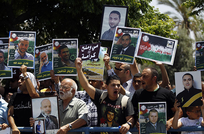 Relatives and friends of Palestinians jailed in Israeli prisons hold placards as they take part in a protest calling for the prisoners release outside Ayalon prison, in the city of Ramle, near Tel Aviv May 23, 2014. (Reuters/Ammar Awad)