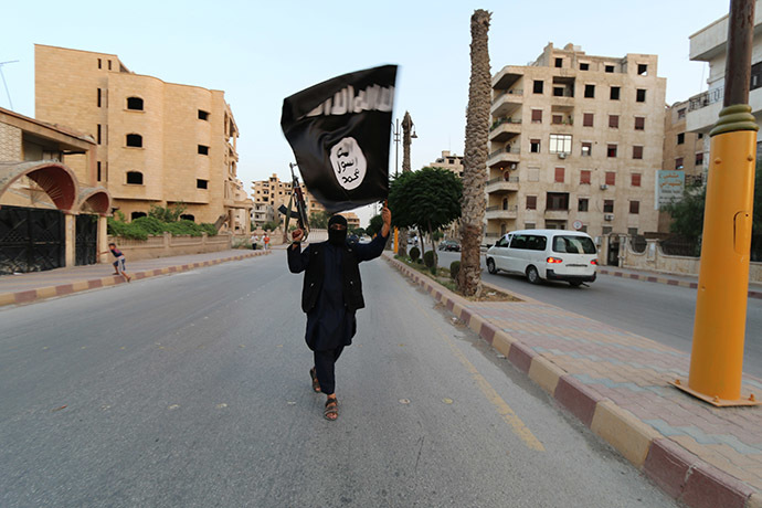 A member loyal to the Islamic State in Iraq and the Levant (ISIL) waves an ISIL flag in Raqqa June 29, 2014. (Reuters/Stringer)