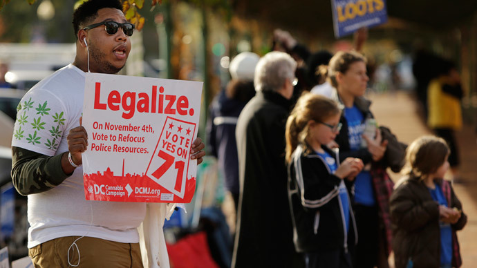 Melvin Clay (L) of the DC Cannabis Campaign holds a sign urging voters to legalize marijuana, at the Eastern Market polling station in Washington November 4, 2014.(Reuters / Gary Cameron)