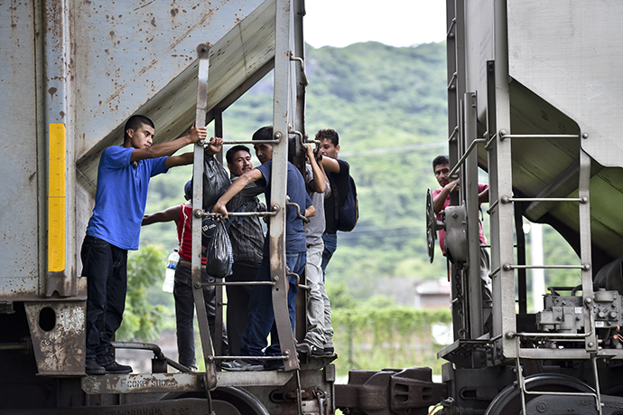 "Central American migrants ride the train called ""The Beast"" in their attemp to reach the border between Mexico and the United States (AFP Photo / Yuri Cortez)"