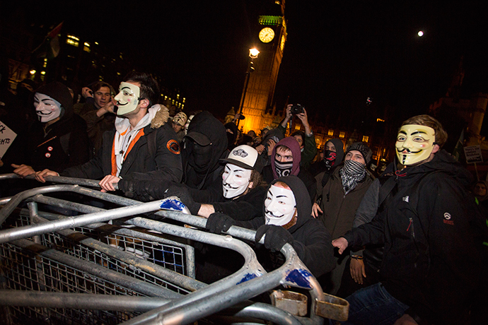 "Anti-capitalist protesters wearing Guy Fawkes masks remove police barrickades during the ""Million Masks March"" in Parliament Square in London on November 5, 2014. (AFP Photo / Jack Taylor)"