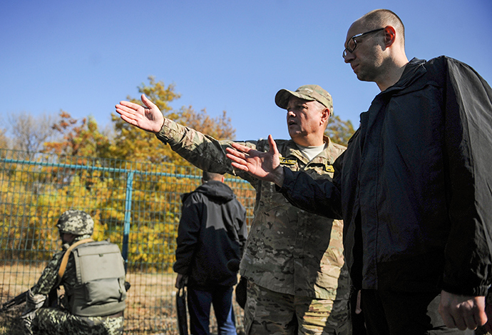 "Ukrainian Prime Minister Arseny Yatseniuk (R) listens to explanations as he inspects the ""Wall"" project, which should reinforce the border with Russia, near Hoptivka border checkpoint in Kharkiv region, October 15, 2014 (Reuters / Andrew Kravchenko)"