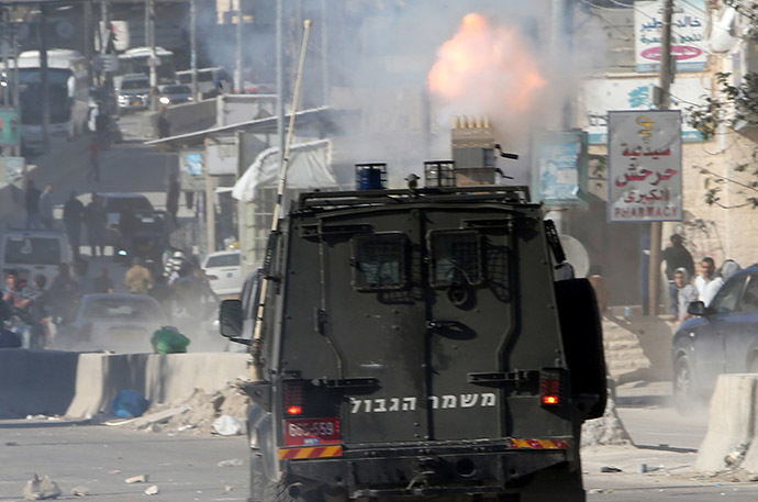 A vehicle of Israeli security forces drives during clashes with Palestinian protesters at the Israeli Qalandia checkpoint between the West Bank city of Ramallah and Jerusalem on November 7, 2014, following a protest against Israel's restrictions at the Al-Aqsa Mosque in Jerusalem. (AFP Photo/Abbas Momani)