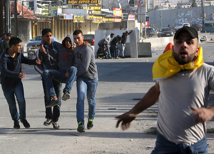 Palestinian youths evacuate a comrade who was injured during clashes with Israeli security forces at the Israeli Qalandia checkpoint between the West Bank city of Ramallah and Jerusalem on November 7, 2014. (AFP Photo/Abbas Momani)