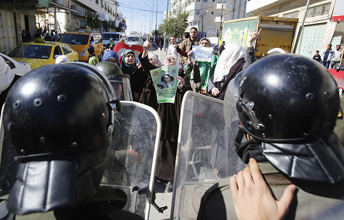 Members of Palestinian security forces take position as Palestinian women take part in an anti-Israel protest against what organizers say are recent visits by Jewish activists to al-Aqsa mosque, in the West Bank city of Hebron November 7, 2014. (Reuters/Mussa Qawasma )