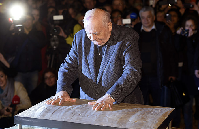 The last ruling President of the Soviet Union Mikhail Gorbachev leaves his handprints in plaster cast bolted onto an original Wall piece from former Checkpoint Charlie border crossing on November 7, 2014 in Berlin. (AFP Photo/Odd Andersen)