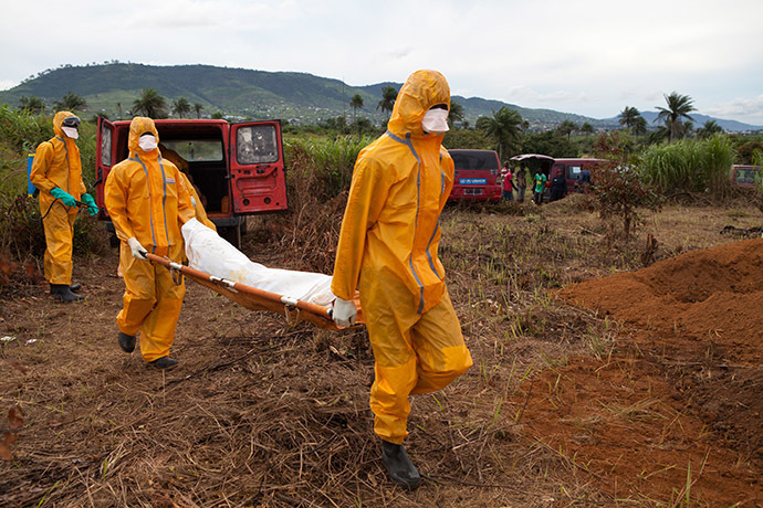 Volunteers in protective suit carry for burial the body of a person who died from Ebola in Waterloo, some 30 kilometers southeast of Freetown, on October 7, 2014.(AFP Photo/Florian Plaucheur)