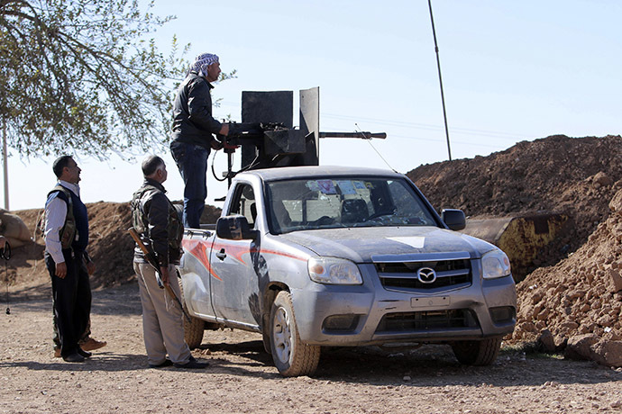A member of the Kurdish People's Protection Units (YPG) aims a weapon mounted on a pick-up truck towards areas controlled by Islamic State fighters in the southern countryside of Ras al-Ain November 7, 2014. (Reuters/Rodi Said)