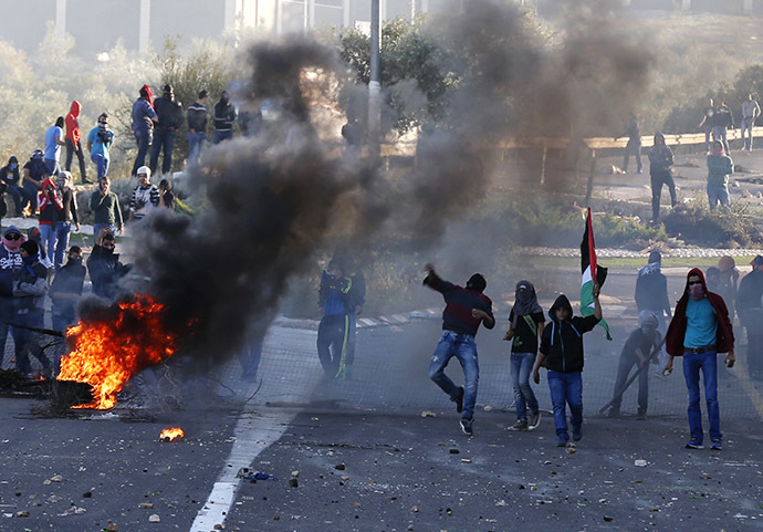 Israeli Arab youths throw stones during clashes with Israeli police at the entrance to the town of Kfar Kanna, in the North of Israel, November 8, 2014. (Reuters/Ammar Awad)