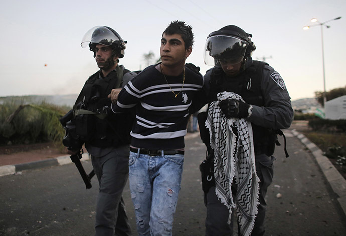 Israeli policemen detain an Arab youth during clashes at the entrance to the town of Kfar Kanna, north of Israel, November 8, 2014. (Reuters/Ammar Awad)
