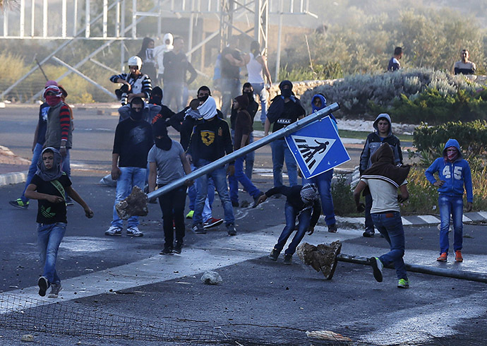 Israeli Arab youths clash with Israeli police at the entrance to the town of Kfar Kanna, North of Israel, November 8, 2014. (Reuters/Ammar Awad)