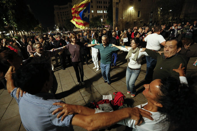 People take part in a Sardana dance, a typical Catalan dance, near the cathedral in Barcelona, November 8, 2014. (Reuters/Gustau Nacarino)
