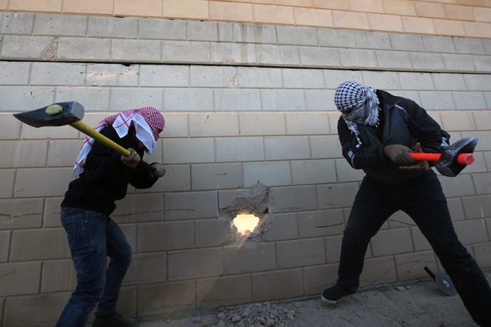 Palestinian youths use sledgehammers to break parts from a concrete segment of the controversial Israeli separation wall in the West Bank village of Bir Nabala -between Jerusalem and Ramallah- on November 8, 2014 as celebrations today mark 25 years since the fall of the Berlin Wall. (AFP Photo)