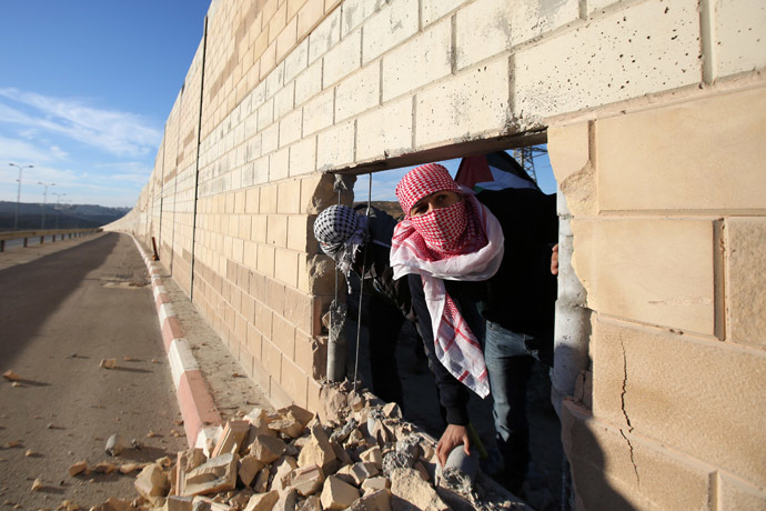 Palestinian youths appear through a hole they dug in the controversial Israeli separation wall in the West Bank village of Bir Nabala -between Jerusalem and Ramallah- on November 8, 2014 as celebrations today mark 25 years since the fall of the Berlin Wall. (AFP Photo)