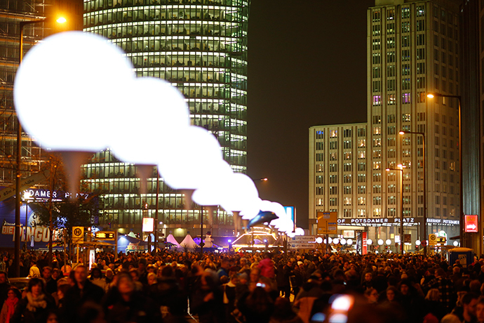 People walk under the lit balloons placed along the former Berlin Wall at Potsdamer Platz as part of the installation 'Lichtgrenze' (Border of Light) in Berlin, November 9, 2014. (Reuters / Hannibal Hanschke)