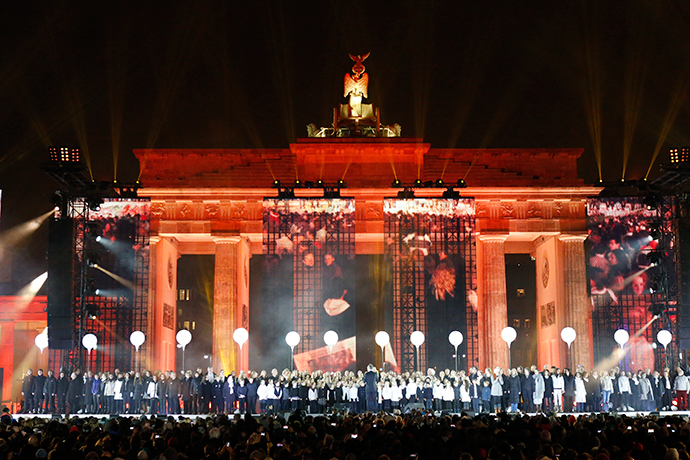A choir performs on stage in front of the Brandenburg Gate next to part of the installation 'Lichtgrenze' (Border of Light) in Berlin, November 9, 2014. (Reuters / Fabrizio Bensch)