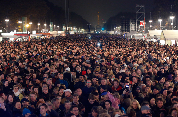 People wait in front of the stage in front of the Brandenburg Gate in Berlin with the landmark Siegessaeule (victory column) pictured in the background, November 9, 2014. (Reuters / Fabrizio Bensch)