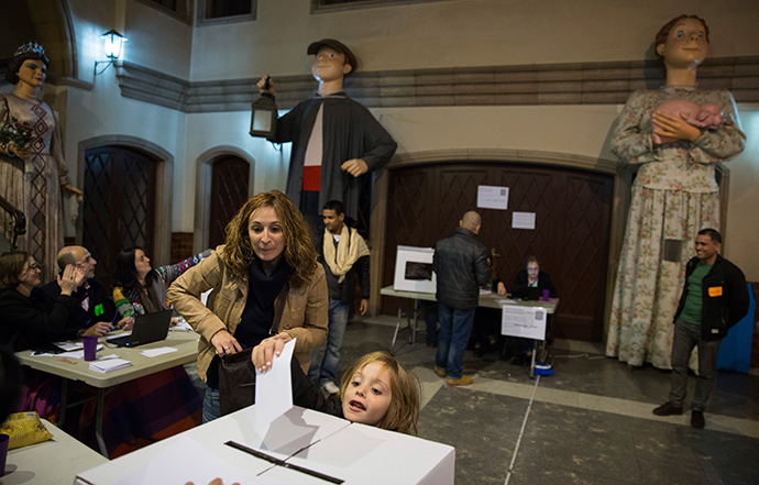 "A child deposits her mother's ballot at a polling station in a school in front of Catalan ""Gegants"", or giant figures, while voting in a symbolic independence vote in Barcelona, November 9, 2014. (Reuters / Paul Hanna)"