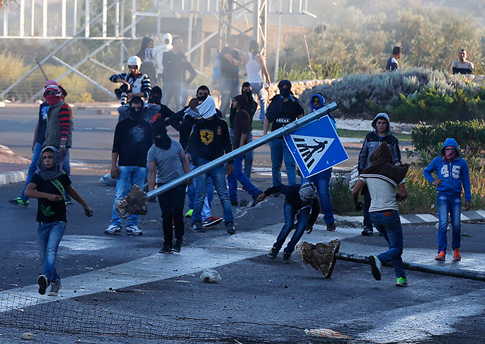 Israeli Arab youths clash with Israeli police at the entrance to the town of Kfar Kanna, in northern Israel, November 8, 2014 (Reuters / Ammar Awad)