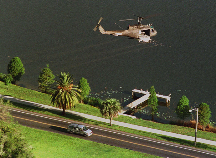 A Huey helicopter sprays malathion on an area near where Mediterranean fruit flies were found in Lakeland, June 21 as motorists pass below. (Reuters)