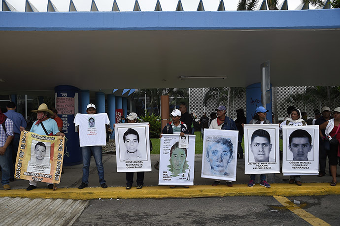 Demonstrators hold pictures of some of the 43 missing students as they block the entrances of the airport during clashes with riot police that erupted during a protest against their suspected massacre, in Acapulco, in the Mexican state of Guerrero State, on November 10, 2014. (AFP Photo/Ronaldo Schemidt)