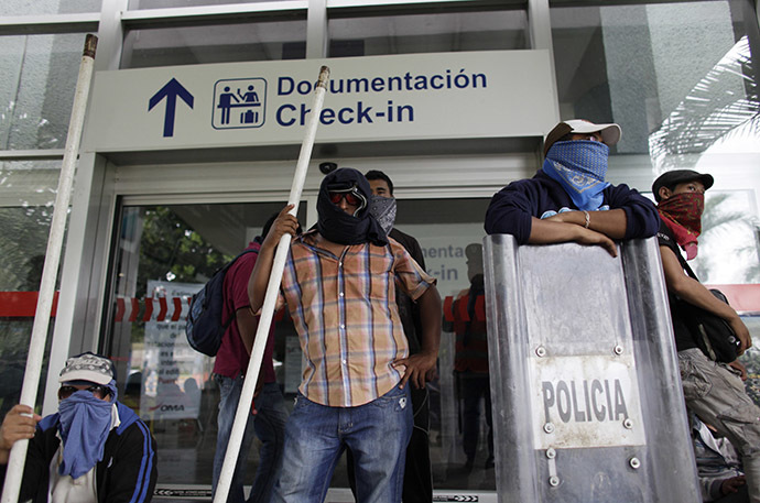 Masked protesters stand outside a building of the airport while blocking the access during a protest in reprisal for the apparent killing of 43 trainee teachers, in Acapulco November 10, 2014. (Reuters/Daniel Becerril)