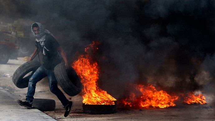 A Palestinian protester carries tyres during clashes with Israeli troops following an anti-Israel demonstration over the recent entry restrictions to the al-Aqsa mosque, at Qalandia checkpoint, near the West Bank city of Ramallah November 2, 2014. (Reuters / Ammar Awad)