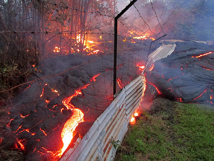 This image provided by the US Geological Survey (USGS) shows lava from the Kilauea volcano in Pahoa, Hawaii from the lobe that was active in the forest below the Pahoa cemetery overcomes a fence marking private property late on the afternoon of October 31, 2014. (AFP Photo/US Geological Survey)