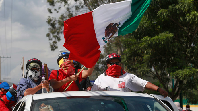 Masked members of CETEG (State Coordinator of Teachers of Guerrero teacher's union), with the Mexican national flag, gather outside the comptroller's office of the Secretary of the Department of Education in Guerrero, in Chilpancingo, November 12, 2014.(Reuters / Jorge Dan Lopez)