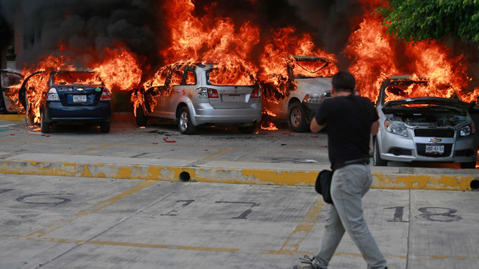 A news photographer take pictures of cars set alight by CETEG (State Coordinator of Teachers of Guerrero teacher's union) members at a City Congress parking lot in Chilpancingo, November 12, 2014.(Reuters / Jorge Dan Lopez)