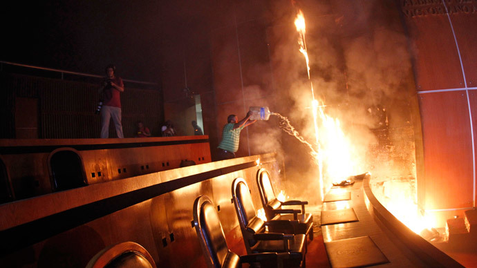 A man tries to extinguish a fire set alight at the principal hall of the City Congress by members of CETEG (State Coordinator of Teachers of Guerrero teacher's union), in Chilpancingo, November 12, 2014. (Reuters / Jorge Dan Lopez)