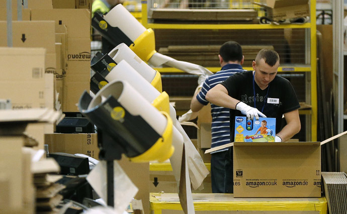 A worker packs completed orders into boxes at the Amazon fulfilment centre in Peterborough, central England (Reuters/Phil Noble)