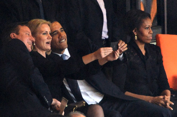 US President Barack Obama (R) and British Prime Minister David Cameron pose for a selfie picture with Denmark's Prime Minister Helle Thorning Schmidt (C) next to US First Lady Michelle Obama (R) during the memorial service of South African former president Nelson Mandela at the FNB Stadium (Soccer City) in Johannesburg on December 10, 2013. (AFP Photo)